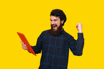 Photo of handsome man with beard is screaming and celebrating with rised arm, while holding a tablet, over yellow wall