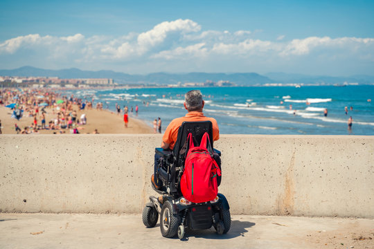 Lonely man on electric wheelchair looking  at the beach. Disabled person at the beach.