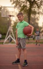 one little boy posing, holding a basketball ball, on a basketball court.