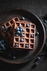 Yummy waffles with dark chocolate and fresh blueberries