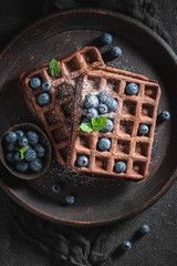 Homemade waffles with dark chocolate and fresh blueberries