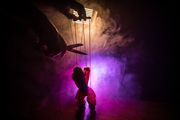 Concept of manipulation. Hand holds strings for manipulation. The hand controls the puppet strings on a dark foggy background.
