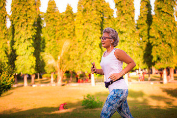 middle aged 40s or 50s happy and attractive woman with grey hair training at city park with green trees on sunrise doing running and jogging workout in health care