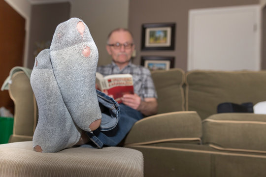 man sitting on couch with holes in his socks