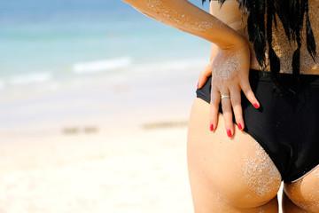Sexy back perfect shape of a tan woman wearing a black bikini