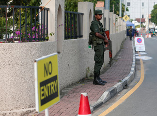 An army soldier stands guard police at the main entrance of the St.Theresa's church as the Catholic churches in Sri Lanka restart their Sunday service after Easter Sunday bombing attacks on 21st of April,in Colombo