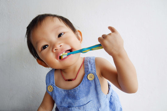 Happy Asian baby girl practice to brushing her teeth. A child aged of one year old on white background. Healthy and kid concept.