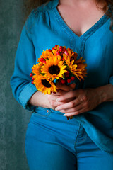 Fototapete - Woman in blue blouse holding bouquet of sunflowers and hypericum berries.