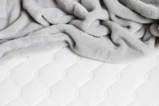 Grey blanket with pompoms on the new mattress.