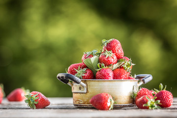 Fresh ripe strawberries in vintage kitchen pot on old garden table
