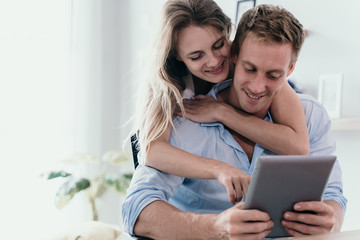 Couple love surfing with digital tablet on the internet in the morning Wall mural