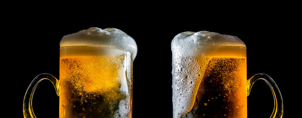 Two large glasses of beer with foam close-up, facing each other, isolated against a black background. Two overflowing glasses of beer with flowing foam.