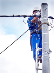 Fototapeta Praca montera instalacji elektrycznej na słupie energetycznym obraz