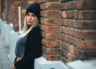 Hipster girl leaning on brick wall