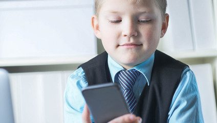 Serious little boy looking at the phone at father's table in office. Boy in business suit playing boss.