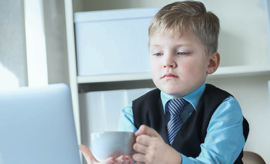 Young business boy working on laptop holding white cup of coffee or hot tea. Funny little boss in office.
