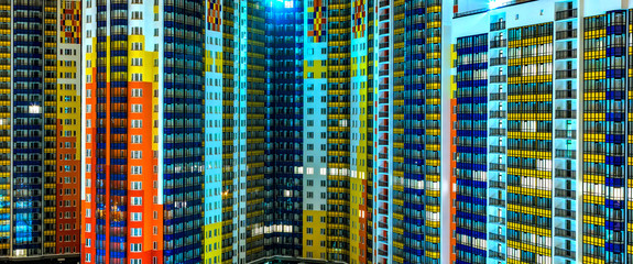 facade of residential apartments in modern metropolis. Night, background texture