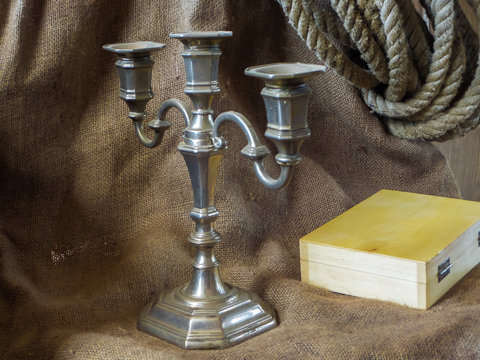 Antique candlestick and a wooden box on the background of burlap and hemp rope.