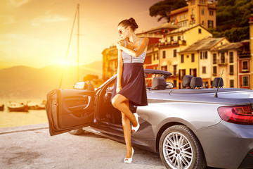 Slim young rich woman with summer car. Portofin port in Italy. Summer sunset time of golden color and background of yachts and boats. Free space for your decoration.