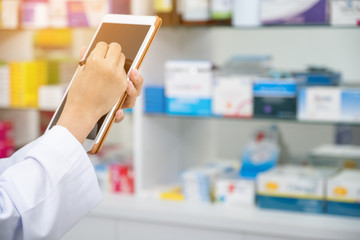Pharmacist working with a tablet computer in the pharmacy holding it in her hand while reading information