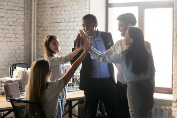 Happy multinational coworkers giving high five celebrating great teamwork result
