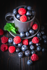 Raspberries and blueberries in a Cup on a dark background. Summer and healthy food concept. Selective focus. Vertical.
