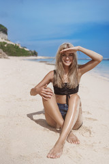 Fotobehang Vertical shot happy woman enjoy summer holiday vacation cover eyes sunlight see camera smiling delighted have fun, relaxing seaside, sit sandy beach tropical island wanna swim ocean surf