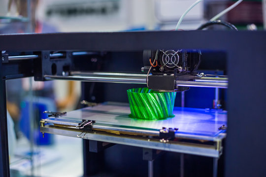 Automatic three dimensional 3D printer machine printing plastic model at modern technology exhibition. 3D printing, additive technologies, 4.0 industrial revolution and futuristic concept