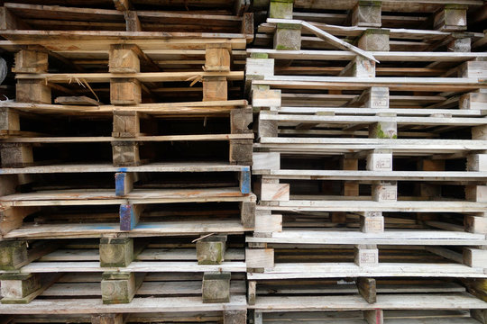 Stacks of old used discarded wooden shipping pallets