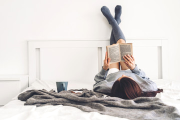 Obraz Young woman relaxing and reading book on bed at home - fototapety do salonu