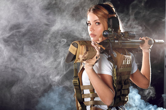 Adorable riot woman with blonde long hair dressed in military style, wearing plate carrier, holding snipper rifleon back, looking at camera in studio over foggy dark background