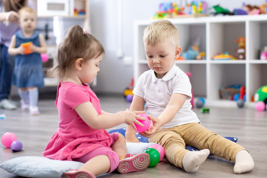 Little toddlers boy and a girl play together in nursery room. Preschool children in day care centre