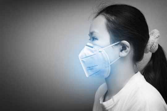 Portrait side view of Asian woman using N95 respirator mask for protecting air pollution