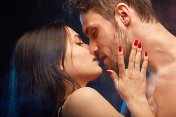 dark-haired woman with red manicure touching her man's face and kissing him. close up photo