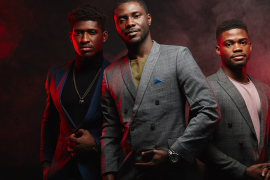 Band of confident popular african musicians or singers in fashionable classy wear making poster for musical magazine cover, posing before camera in studio