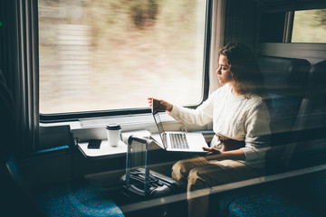 Freelancer girl working with laptop in the train, business travel or technology concept. Wall mural