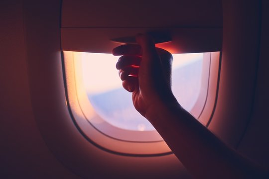 Close-up airplane window at sunrise