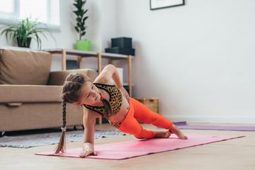 Little girl doing plank exercise at home.