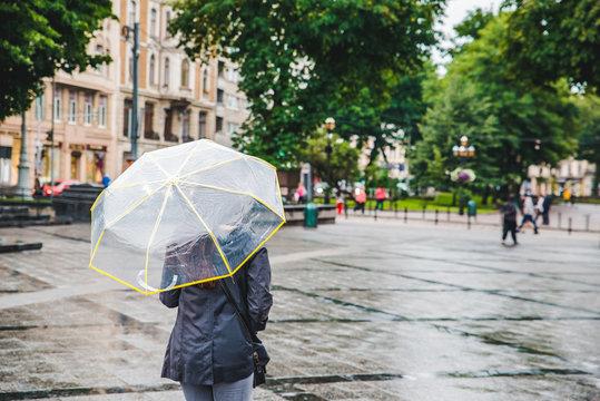 woman walking by wet rainy streets under transparent umbrella
