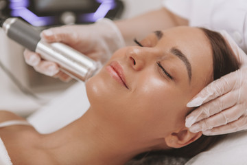 Gorgeous happy young woman with perfect skin smiling with her eyes closed, getting facial treatment at beautician office. Professional cosmetologist performing microcurrent face skin procedure