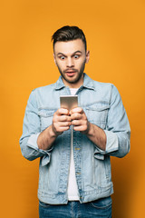 Young modern stylish man in denim is using smartphone in his hands while standing over yellow background