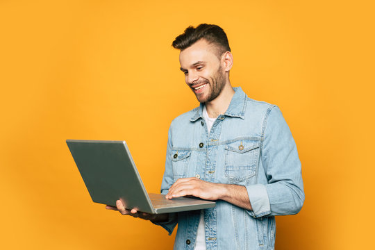 Modern young student or business man is working with laptop in hands on yellow background