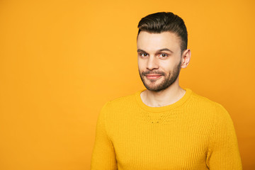 Close up portrait of happy handsome man in yellow is posing over orange background