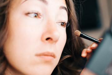 Woman applying cosmetics eyeshadow with brush.