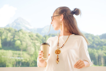 Beautiful woman with cup of coffee enjoying view of mountains.