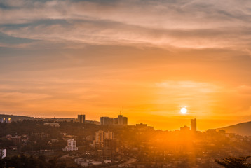 Kigali city centre skyline and surrounding areas under a golden sky at sunset