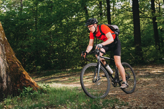 Mountain biker riding on bike in spring inspirational forest landscape. Man cycling MTB on enduro trail track. Sport fitness motivation and inspiration.