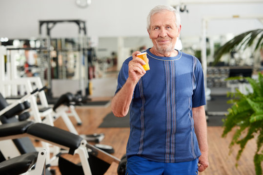 Senior man with pills at gym. Senior man with bottle of supplement at fitness studio. People, sport and health care concept.