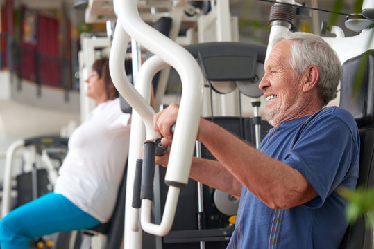 Senior man training on machine at fitness center. High-intensity workouts for senior people. Sport and workout concept.
