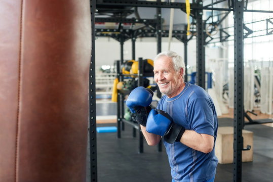 Handsome senior male training with punching bag. Old trainer training with punching bag in fitness studio. People, sport, active way of life.